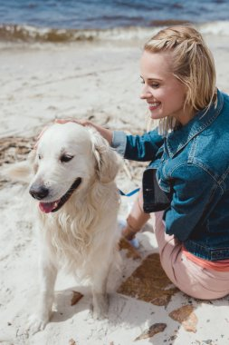 attractive woman sitting with golden retriever dog on sandy shore
