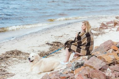 blonde woman wrapped in blanket sitting on sea shore with dog