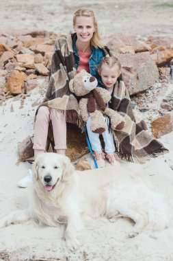 attractive mother and daughter in blanket sitting with dog on shore