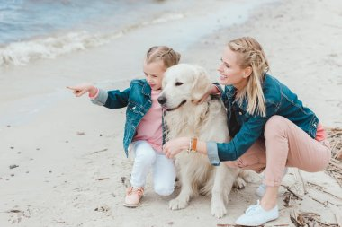 family with golden retriever dog on sea shore, daughter pointing somewhere