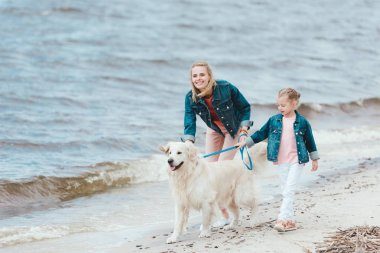 happy family walking with golden retriever on sea shore