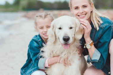 smiling mother and daughter with golden retriever dog