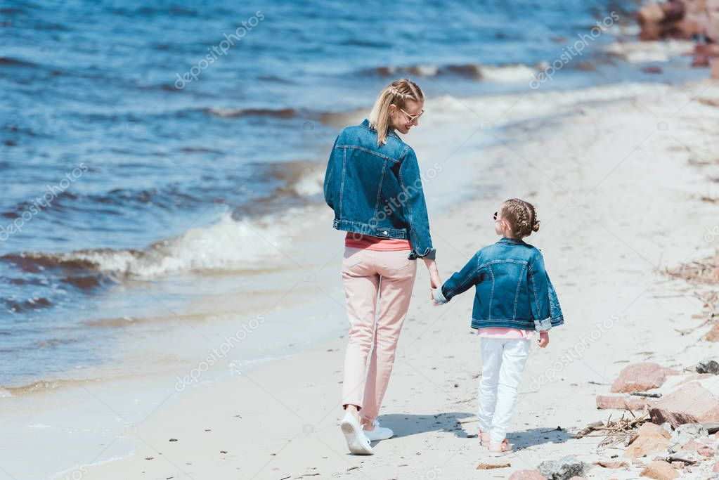 rear view of mom and daughter holding hands and walking on sea shore