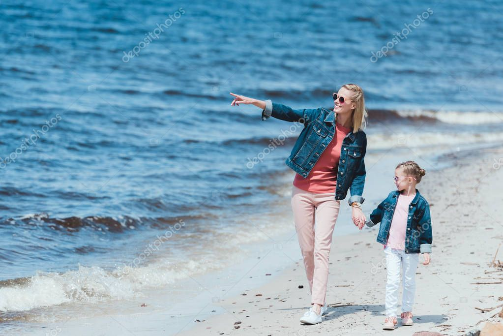 beautiful mom and daughter holding hands and walking on sea shore, mother showing something