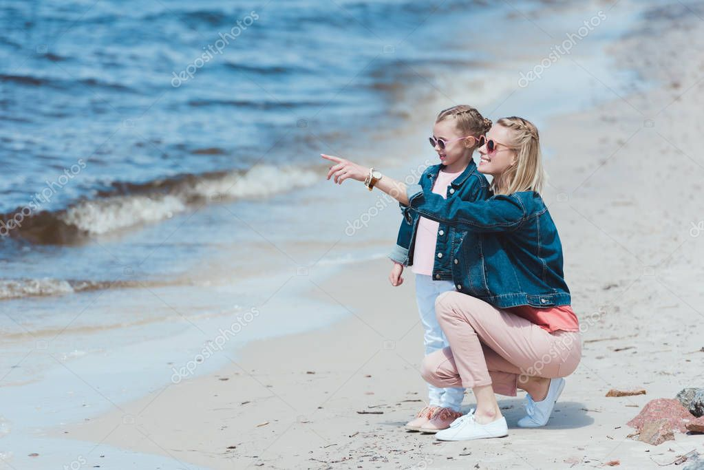 mother showing something to her daughter on sea shore