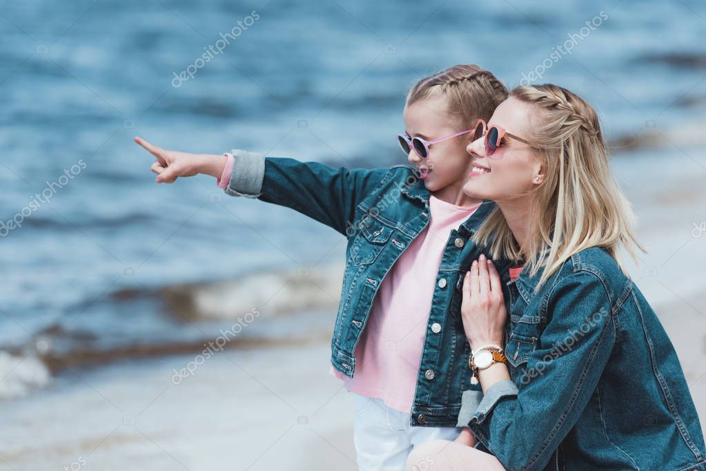 adorable daughter showing something to her mother in the sea