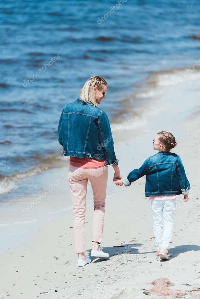 back view of stylish mother and daughter holding hands and walking on shore