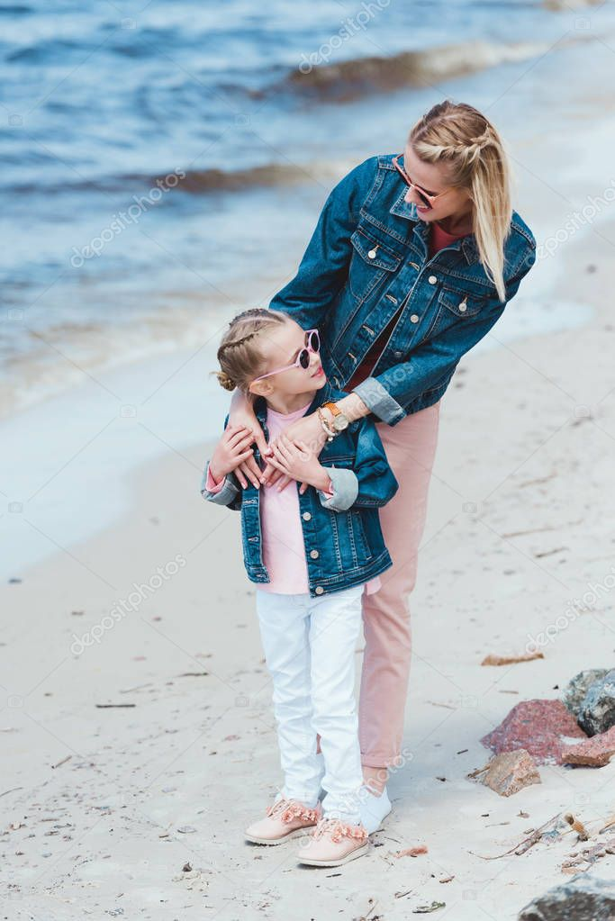 attractive mother and adorable daughter in sunglasses embracing on sea shore
