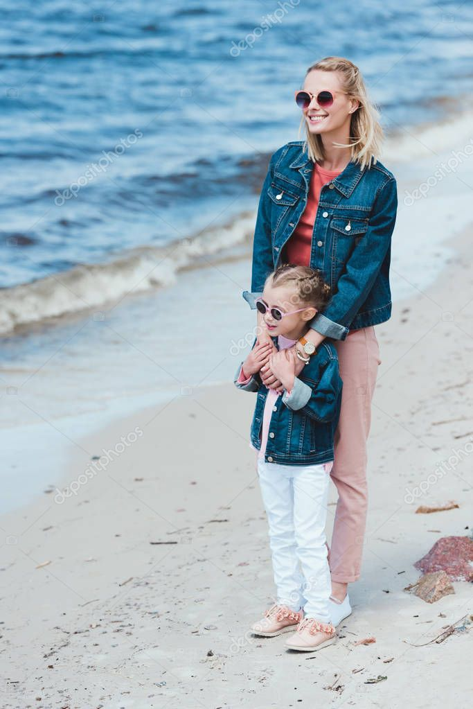 stylish mother and daughter in sunglasses hugging on sea shore