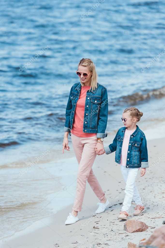 happy stylish mother and daughter holding hands and walking on sea stylish