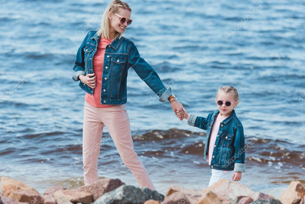 stylish mother and child in sunglasses holding hands and walking on sea shore