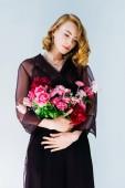 Fotografie krásná zamyšlená mladá žena držící něžně růžové květy izolované Grey