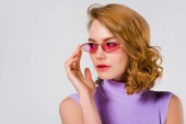 Photo portrait of beautiful young woman in pink sunglasses looking away isolated on grey