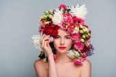 portrait of beautiful young naked woman in floral wreath looking at camera isolated on grey