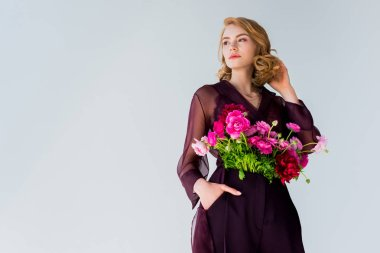 low angle view of elegant young woman with beautiful flowers looking away isolated on grey