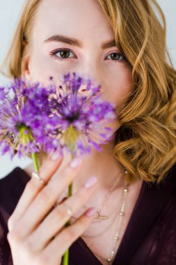 beautiful young woman holding fresh purple flowers and looking at camera isolated on grey