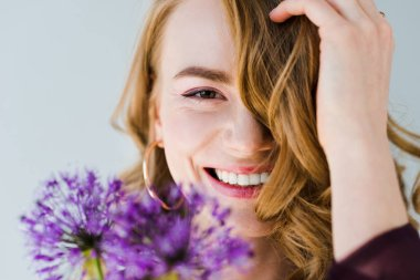 beautiful girl holding fresh violet flowers and smiling at camera isolated on grey