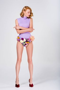 full length view of beautiful girl in panties made of flowers and high heeled shoes standing with crossed arms on grey