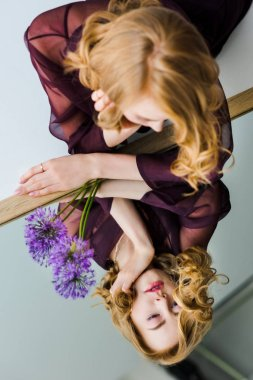 young woman looking at reflection while lying on mirror with violet flowers
