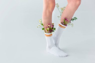 partial view of young woman in socks with beautiful fresh flowers isolated on grey