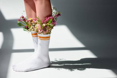 cropped shot of young woman with beautiful flowers in socks standing on grey