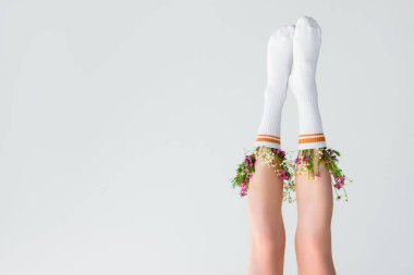 Upside down view of female legs with fresh flowers in socks isolated on grey stock vector