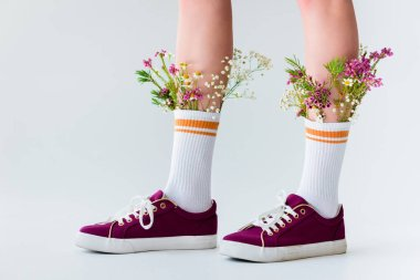 close-up partial view of female legs with beautiful flowers in socks isolated on grey