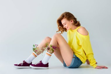 side view of beautiful smiling girl with flowers in socks sitting isolated on grey