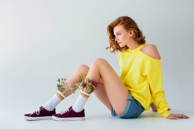 side view of beautiful girl with flowers in socks sitting and looking away isolated on grey