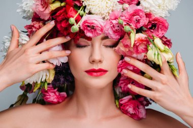 Portrait of gorgeous young woman with closed eyes posing with beautiful flowers on head isolated on grey stock vector