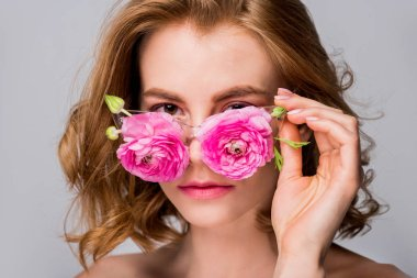 beautiful girl wearing eyeglasses with flowers and looking at camera isolated on grey