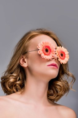 low angle view of naked girl wearing glasses with flowers isolated on grey