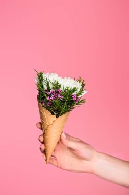 cropped shot of girl holding waffle cone with beautiful flowers isolated on pink