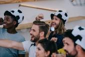 Fotografie glücklich multikulturellen Freunde im Fußball ball Hüte feiern, Gestikulieren mit den Händen und beobachten Fußballspiel auf Bar