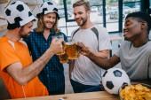 Fényképek mosolygó multikulturális csoport férfi Labdarúgás rajongók pohár közben néz foci felel meg a csengő sört bar