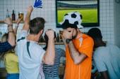 Fotografie frustrierter junger Mann im Fußball Ball Hut Fan T-shirt Holding Deckung und Augen von hand Palm während seiner Freunde feiern und tut ja Gesten während der Uhr des Fußballs auf TV-Bildschirm in entsprechen Bar