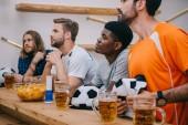 Fényképek multikulturális csoport férfi szurkolók futball labda sapka, rajongó kürt, chipek és nézi labdarúgó mérkőzés a sört bar