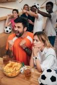 Fotografie emotionale multikulturelle Fußball-fans mit den Fingern zeigen und beobachten Fußballspiel in Bar mit Chips und Biergläser