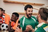 Fényképek izgatott a szurkolók a zöld t-shirt ünnepelte a győzelmet, míg ideges barátaik a különböző t-shirt közben néz, az foci labda mögött ülve egyezik a bar