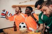 Fényképek mosolyogva multikulturális szurkolók, pólókat és különböző trikók néz foci közben ül a labdát, miközben a ideges meg győzelmet ünneplő kendő felel meg a narancssárga sáv