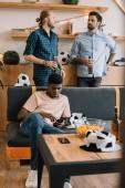 Fotografie Afrikanische amerikanische Jüngling mit Smartphone auf Sofa, während seine Freunde reden mit Bierflaschen hinter zu Hause