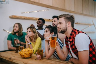 focused multicultural friends with beer and chips watching soccer match at bar