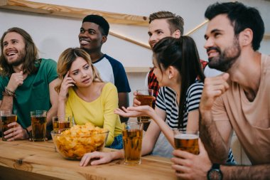group of multicultural friends with beer and chips watching soccer match at bar