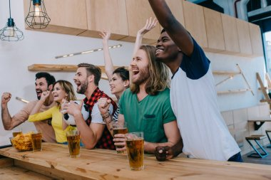Excited multicultural friends celebrating, gesturing by hands and watching football match at bar stock vector