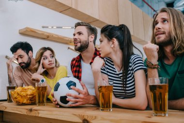 group of emotional friends sitting at bar counter with soccer ball, beer and chips during watch of football match