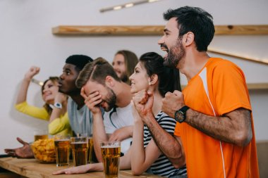 side view of emotional multicultural friends gesturing by hands and watching football match at bar with beer glasses and chips
