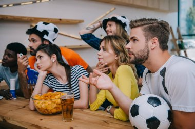 upset young multicultural friends in soccer ball hats with hand clappers and fan horn watching football match at bar