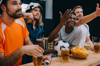 smiling multicultural group of male football fans gesturing by hands and watching soccer match at bar