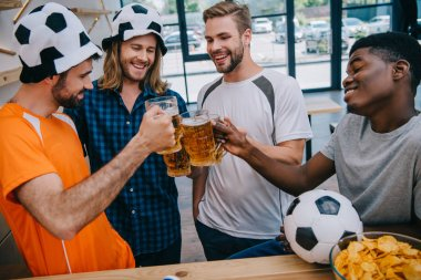 smiling multicultural group of male football fans clinking beer glasses during watch of soccer match at bar