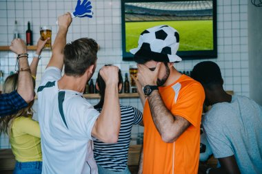 frustrated young man in soccer ball hat and fan t-shirt holding covering eyes by hand palm while his friends celebrating and doing yes gestures during watch of soccer match on tv screen at bar